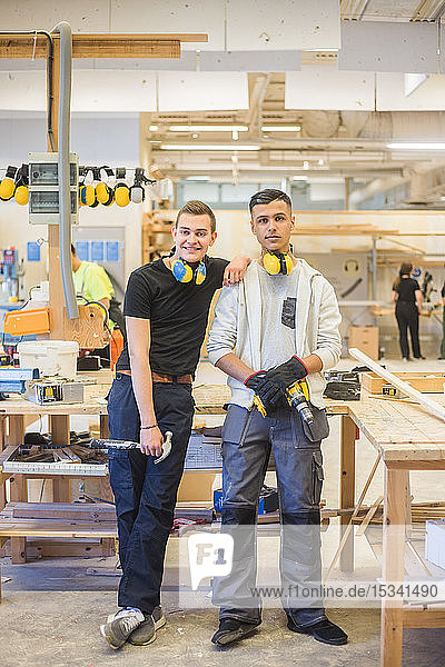 Lächelnder junger männlicher Auszubildender in voller Länge  der sich auf die Schulter eines Mitarbeiters stützt  während er in der Werkstatt Arbeitswerkzeuge hält