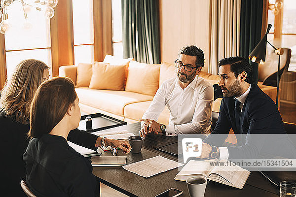 Männliche und weibliche juristische Mitarbeiter  die eine Sitzung im Sitzungssaal planen