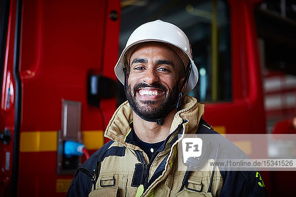 Portrait of smiling firefighter wearing helmet standing at fire station