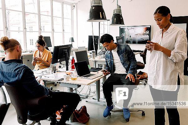 Männliche und weibliche Mitarbeiter nutzen Smartphones im Büro