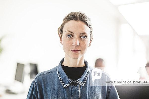 Porträt einer selbstbewussten Geschäftsfrau  die im Kreativbüro steht