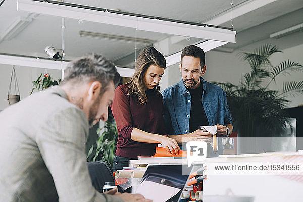 Geschäftsmann und Geschäftsfrau diskutieren  während ein männlicher Kollege im Kreativbüro am Laptop arbeitet
