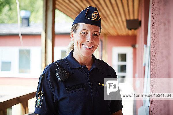 Porträt einer lächelnden Polizistin mit Mütze auf dem Balkon eines Polizeireviers