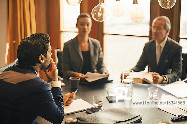 Male legal advisor discussing with colleagues in meeting at legal office
