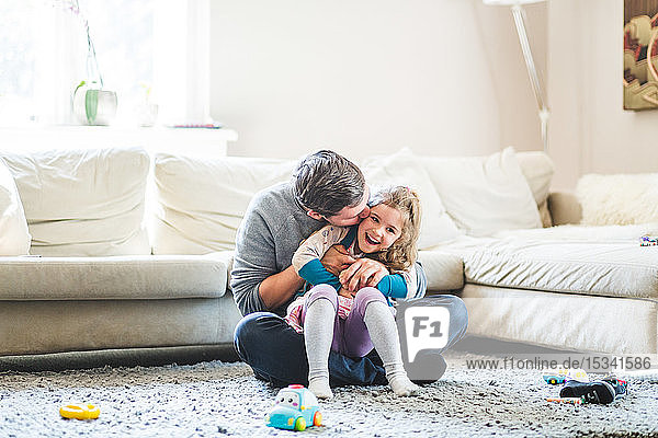 Mid adult man kissing daughter while sitting on carpet at home