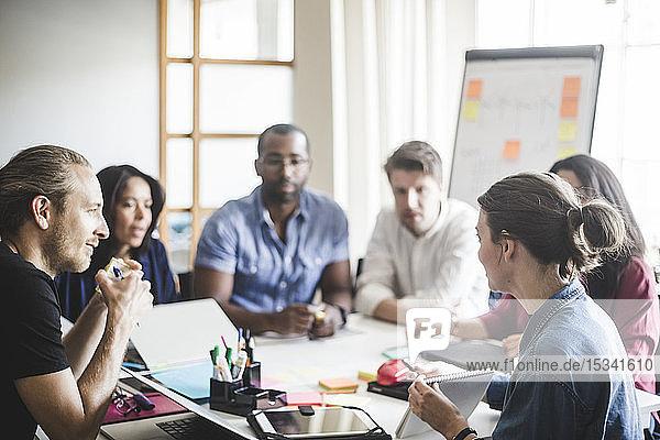 Geschäftsfrau zeigt Tagebuch  während sie ihren Kollegen bei einer Besprechung im Büro den Geschäftsplan erklärt