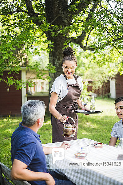 Smiling young female waitress serving drink for male customers sitting at outdoor cafe