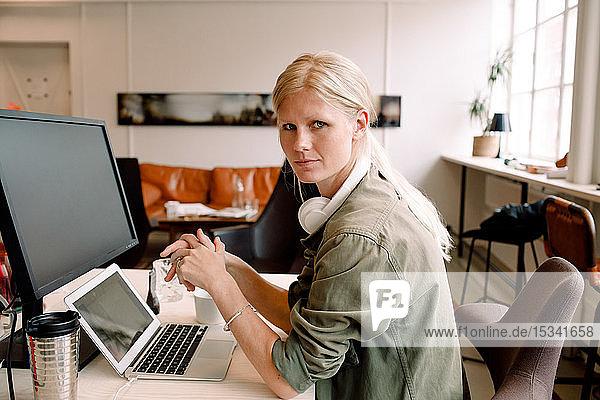Porträt einer Unternehmerin  die am Arbeitsplatz auf einem Stuhl sitzt