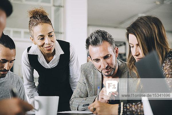 Kreative Geschäftsleute schauen auf Kolleginnen  die im Büro am Tisch schreiben