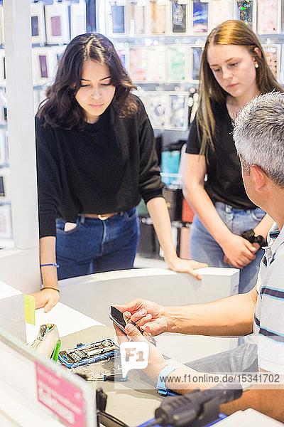 Junge weibliche Auszubildende schauen auf Handy  während sie dem männlichen Besitzer zuhören  der am Schreibtisch in der Werkstatt sitzt