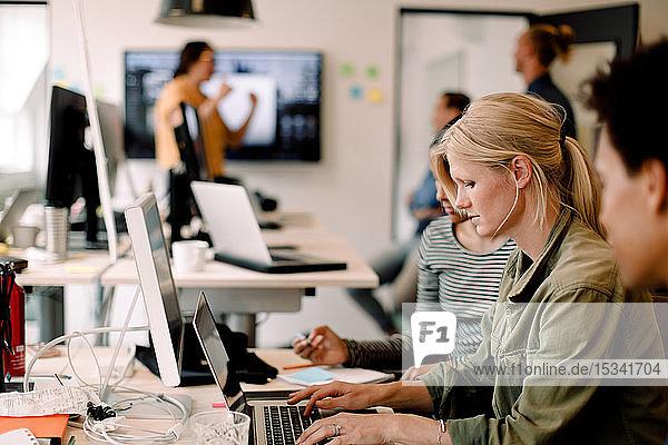 Weibliche Führungskraft tippt am Laptop  während sie bei Kollegen im Kreativbüro sitzt