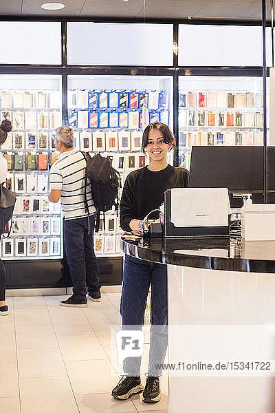 Porträt einer selbstbewussten Verkäuferin in voller Länge  die an der Kasse gegen Kunden im Laden steht