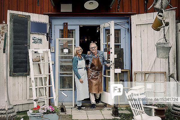 Ganzflächiges Porträt selbstbewusster älterer Mitarbeiter  die an der Tür eines Eisenwarenladens stehen
