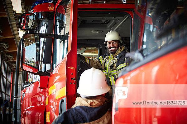 Lächelnder Feuerwehrmann im Gespräch mit einem Kollegen  während er im Feuerwehrauto der Feuerwache sitzt