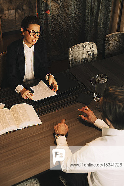 High angle view of client discussing problems with female lawyer in meeting