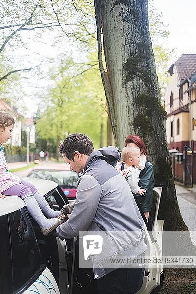 Vater trägt Schuhe zu Tochter auf Auto sitzend