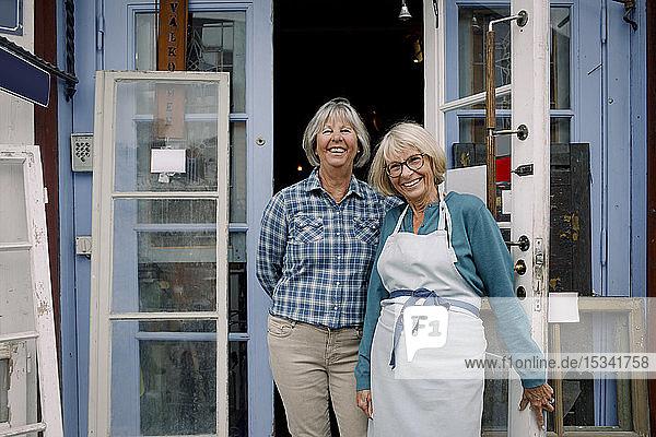Porträt von fröhlichen Besitzerinnen  die am Eingang des Geschäfts stehen