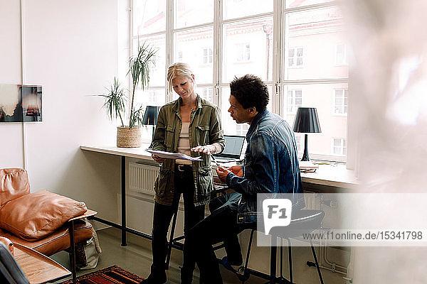 Geschäftsleute diskutieren während ihrer Arbeit im Büro über ein Dokument