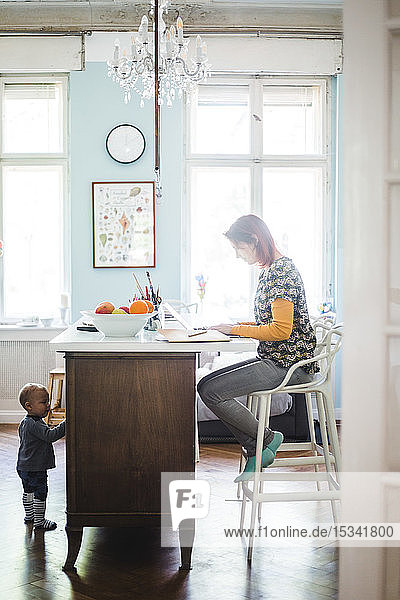 Frau in voller Länge am Laptop arbeitend  während der Sohn zu Hause an der Kücheninsel steht