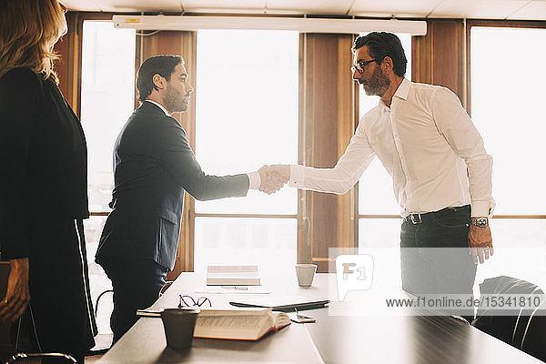 Geschäftsmann schüttelt männlichem Anwalt nach Sitzung im Sitzungssaal die Hand