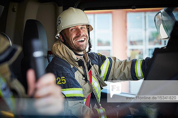 Lächelnder Feuerwehrmann sieht seinen Kollegen an  während er im Feuerwehrauto sitzt