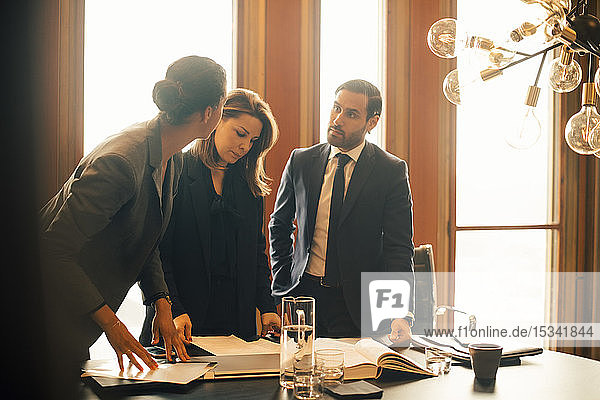 Male and female legal professionals discussing over documents at office meeting