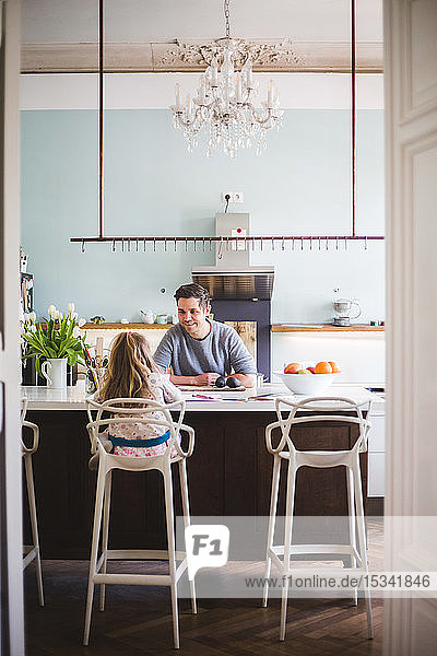 Smiling father looking at girl studying while sitting by kitchen island