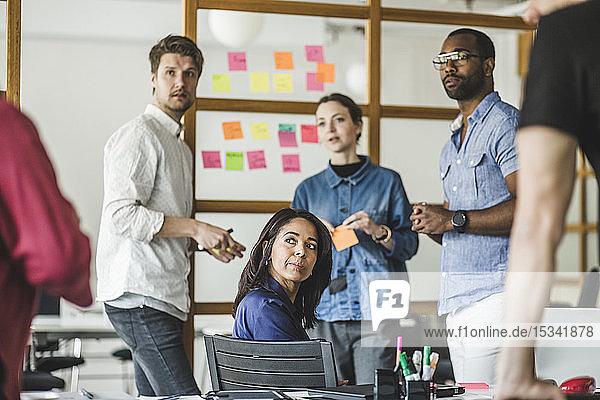 Männliche und weibliche Kollegen  die im Sitzungssaal des Kreativbüros arbeiten