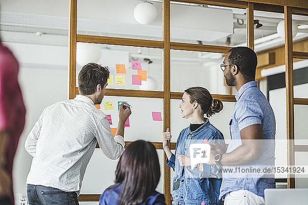 Geschäftsmann schreibt auf Haftnotizen  während er bei einer Besprechung im Kreativbüro mit Kollegen diskutiert