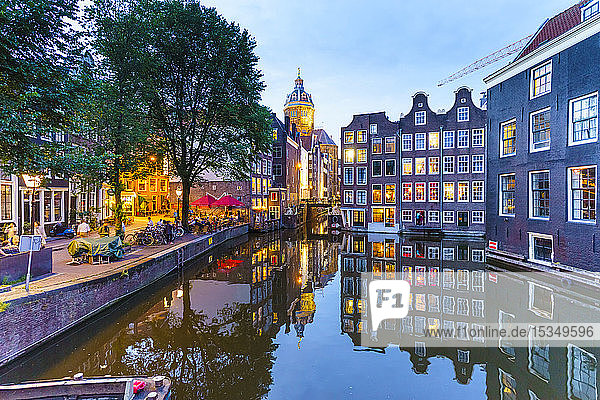 Old gabled buildings by a canal at dusk  Oudezijds Kolk  Amsterdam  North Holland  The Netherlands  Europe