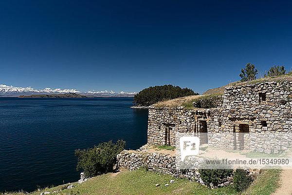 View across deep blue Lake Titicaca with the ruins of the Inca Pilocaina Sun Temple  from Sun Island  Lake Titicaca  Bolivia  South America
