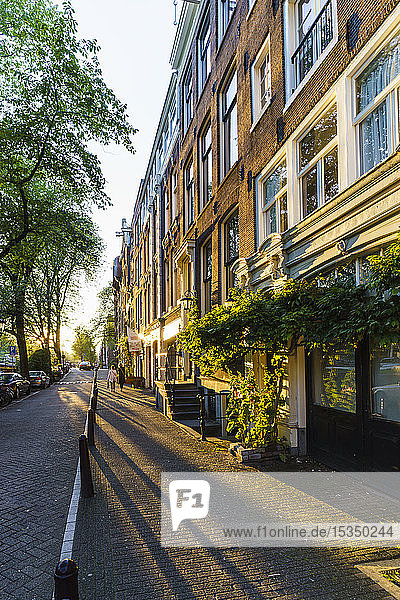 Golden hour light on canalside buildings  Amsterdam  North Holland  The Netherlands  Europe