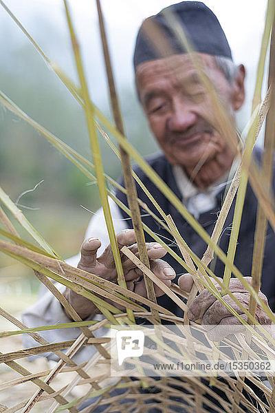 A old Nepali man makes a traditional basket by weaving bamboo  Kathmandu Valley  Nepal  Asia