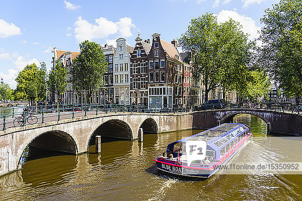 Tourist boat crossing Keisersgracht Canal  Amsterdam  North Holland  The Netherlands  Europe