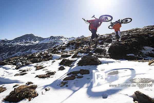 Mountain bikers carry their bikes up a snow covered hillside in the Nepal Himalayas with views of the Langtang mountain range  Nepal  Asia