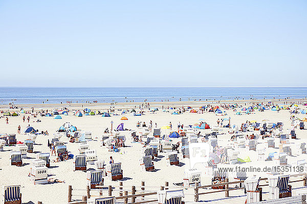 Vast beach with roofed wicker beach chairs on wooden plateaus and people celebrating the summer  Sankt Peter Ording  Schleswig Holstein  Germany  Europe