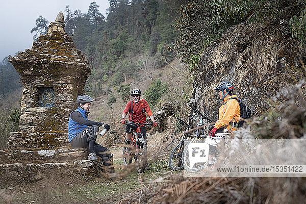Mountain bikers take a break near a moss covered Tibetan chorten in the Himalayas in the Gosainkund region  Nepal  Asia