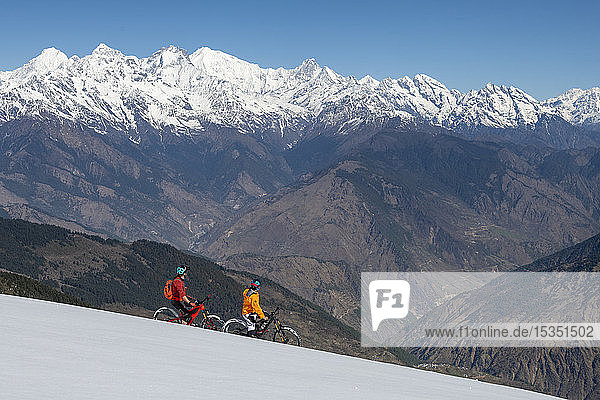 Mountain biking on a snow covered slope in the Himalayas with views of the Langtang mountain range in the distance  Nepal  Asia