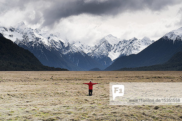 Man in red coat stood holding out his arms looking at snow capped mountains  Fiordland National Park  UNESCO World Heritage Site  South Island  New Zealand  Pacific