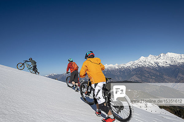 Mountain bikers cycle along a snow covered slope in the Himalayas with views of the Langtang range in the distance  Nepal  Asia