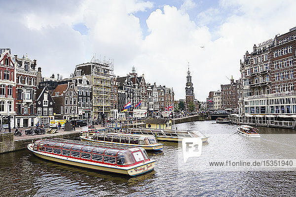 Tourist boats on Amstel River near Muntplein and Rokin  Amsterdam  North Holland  The Netherlands  Europe