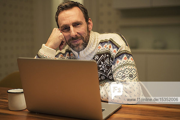 Casual businessman using laptop on table at home