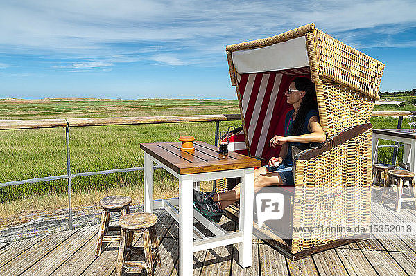 Germany  Schleswig-Holstein  Sankt Peter-Ording  woman sitting in hooded beach chair