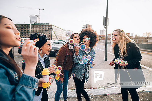 Friends celebrating with confetti and soap bubbles in street  Milan  Italy