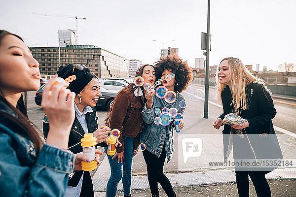 Freunde feiern mit Konfetti und Seifenblasen auf der Straße  Mailand  Italien