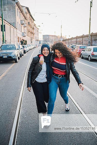 Junge Frau im Hidschab und beste Freundin überqueren Straße in der Stadt