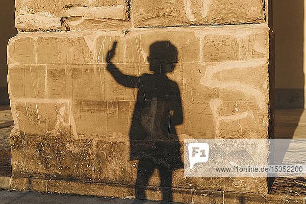 Schatten einer Frau  die sich an einer Steinmauer vergreift