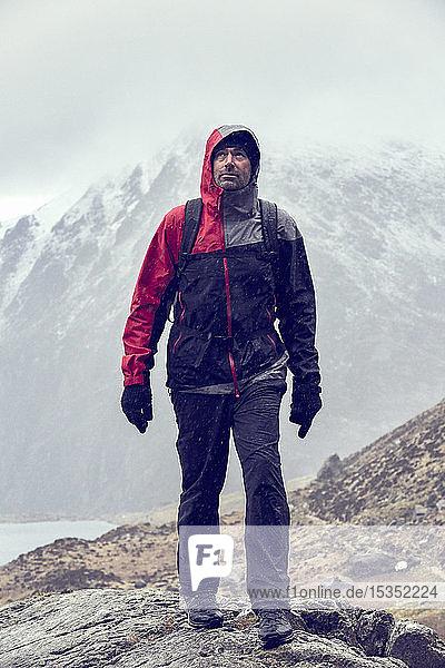 Männlicher Wanderer blickt beim Wandern in zerklüfteter Landschaft mit schneebedeckten Bergen auf  Llanberis  Gwynedd  Wales
