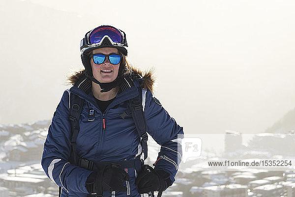 Reife Skifahrerin über schneebedeckten Dächern  Porträt  Alpe-d'Huez  Rhône-Alpes  Frankreich