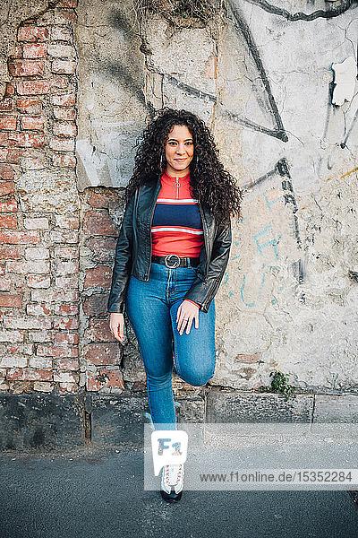 Mittelgroße erwachsene Frau mit langem lockigem Haar  die auf dem Bürgersteig der Stadt an einer Wand lehnt  Porträt